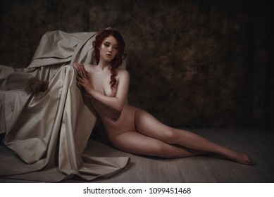 Fine art portrait of naked redhead woman sitting near an old armchair. Conceptual artistic photo of a sexy lady in a retro interior