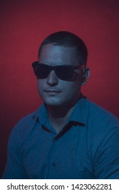 Fine art portrait in red and blue of a young man wearing shades or dark glasses looking at camera with an enigmatic serious expression, moody dark with vignette