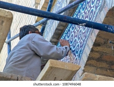 Fine art restorer renovating colorful painting of ancient building. High-rise works on scaffold without protective equipment.