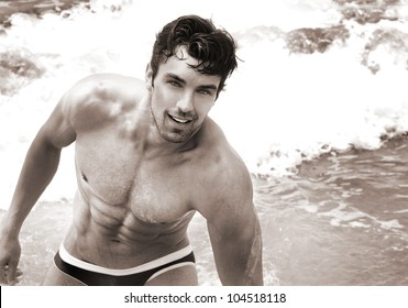 Fine art sepia toned portrait of beautiful young fit man at the beach