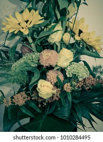 Fine art still life color floral macro close up of a summer flower bouquet with sunflowers, roses,dahlias, celosia and a lot of green grass and leaves in desaturated vintage style
