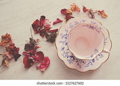 Fine china pink and blue teacup surrounded by dried red rose petals