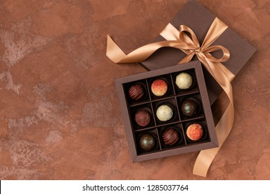 Fine chocolates in craft box with satin ribbon on a dark background. Place for design. Flat layout. Festive concept.