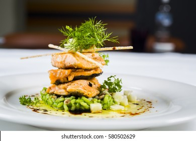 Fine dining, fish fillet breaded in herbs and spice on vegetable risotto.