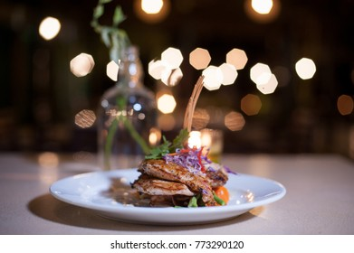 Fine Dining Food Close up.Mixed menu of grilled seafood and beef served on white plate with decoration and Bokeh background.Fine Dining culinary art.