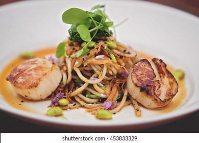 Fine dining food, scallops and udon noodles with kim-chee and edamame