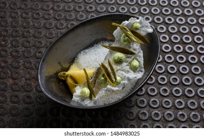 Fine dining ravioli with white fish and grean peas