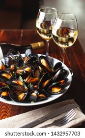 Fine dining in a seafood restaurant: a big dish of mussels with bottle of white wine with two wine glasses, on dark background