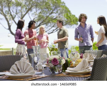 Fine dining table setting with friends enjoying drinks in background
