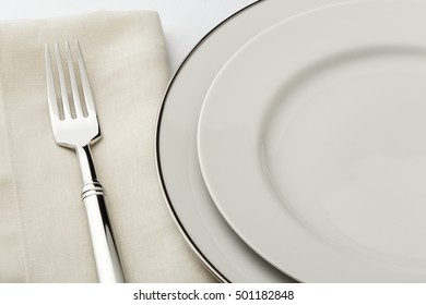 Fine dining table setting place setting with classic style white china dishes, linen napkin and silverware fork