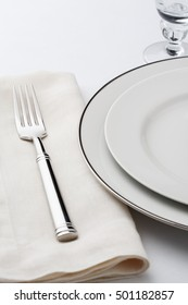 Fine dining table setting place setting with classic white china dishes, linen napkin and silverware fork. Selective focus on tines of fork.