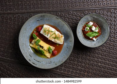 Fine dining, white fish fillet breaded in herbs and spice with homemade ravioli and tomato sauce