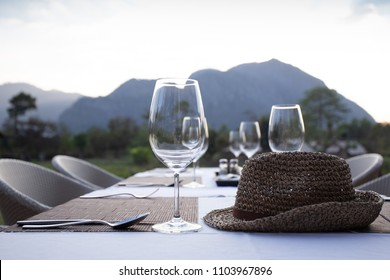 A fine dinner table set with high wine glass and utensils with a weave hat on the table with mountain view.