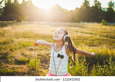 fine girl listening music with headphones and dancing, cute child enjoying music and resting