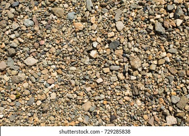 Fine gravel of warm color, texture of road stone of fine fraction.
