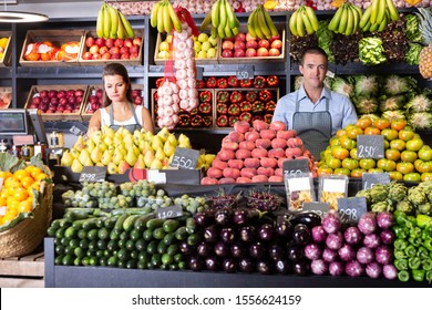 Fine male and female shop assistants in vegetable shop