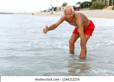 Fine mature man checks the water temperature on the beach