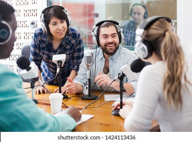 Fine presenters of different nationalities in sound broadcasting station hosting live radio show