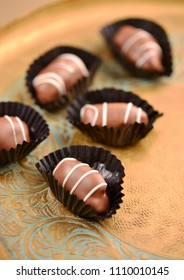 Fine quality gourmet date chocolates. close up of few dates in a golden tray.