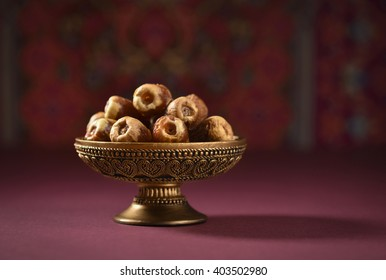 Fine quality ripen dates and an vintage plate. An ornamental bowl of Arabian dates.