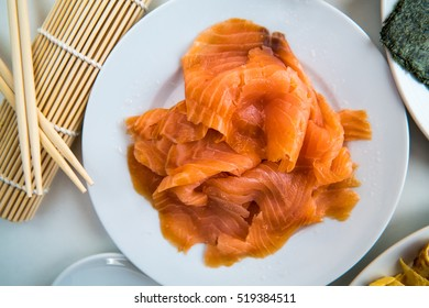 Fine salmon fillet prepared for sushi on a white plate