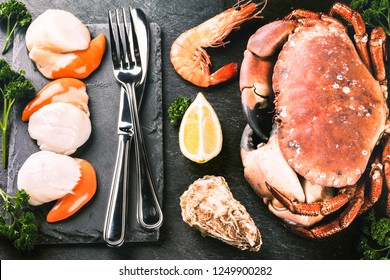 Fine selection of crustacean for dinner. Crab, scallops and oysters with cutlery over dark background