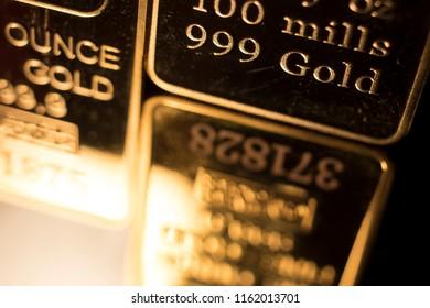 Fine solid gold 999.9 one ounce bullion ingot precious metals bar closeup isolated photo.