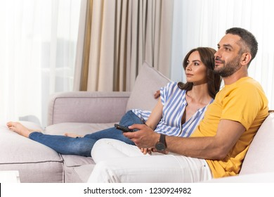 Fine weekend. Beautiful woman and smiling man is watching TV in their light flat. Copy space in left side