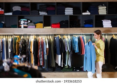 Fine woman shopping casual clothes in modern men store