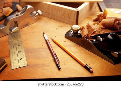 Fine wood working. Saw, hand plane, pencils and a wooden shavings on a work desk under incandescent light.Focus is on forehand side of two pens.