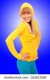 Fine young woman in yellow jacket, on blue background.
