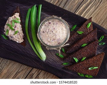 finely chopped salted herring, red onion, egg, apple, and butter mix served in glass jar with rye bread on black serving board and wooden background