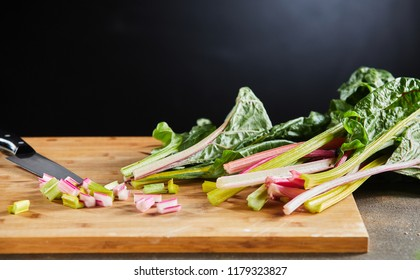 Finely diced fresh Swiss chard or mangold on a wooden chopping board low angle against a dark background and copy space