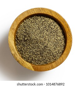 Finely ground black pepper in dark wood bowl isolated on white from above.