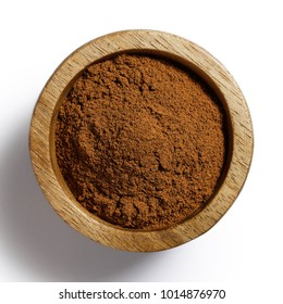Finely ground cinnamon in dark wood bowl isolated on white from above.