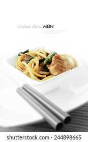 Finest Chicken Chow Mein plated within white asian china against a white background with genuine bamboo chopsticks. Copy space.