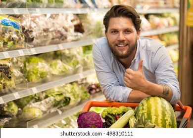 Finest food at this store. Handsome bearded man showing thumbs up smiling cheerfully leaning on his shopping cart, happy customer posing at the supermarket copyspace