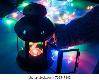 finger of 25s to 35s girl with winter cloth arrange and lighting the red candle in black lantern in the night from christmas celebration event with soft focus decoration light background