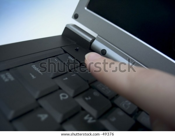 Finger about to press the escape key on a laptop. Focus on the esc. key.