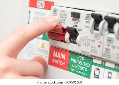 Ein Finger ist dabei, einen großen roten MAINS-Schalter auf einer RCD-Leistungsschalter-Platine auszuschalten