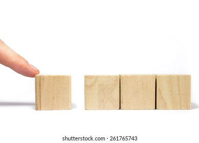 A Finger Adding One Wood Block To A Row Of Three Wood Blocks