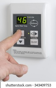 Finger adjusting the temperature on the home gas thermostat