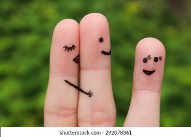 Finger art of couple. Girlfriend hugs and kisses man, and he's flirting with another woman. Concept is not shared love.