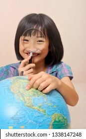 Finger of asian little girl pointing to show a country over the globe in pink background.