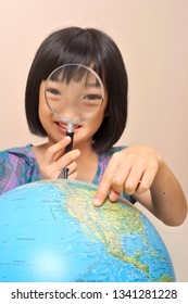 Finger of asian little girl pointing to show a country over the globe while searching by magnifying glass in pink background.