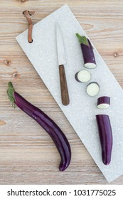 Finger aubergines with a knife and a cutting board from Mamor on a wooden table