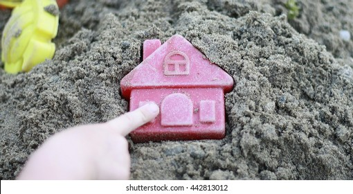 Finger child touches the house on the sand. Bright plastic toys in the sandbox or on the beach. Sandbox, background, children, hand, home, house, buy, purchase, housing, business.