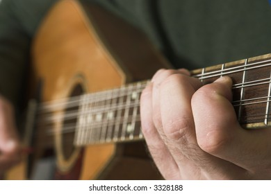 finger close up of man playing guitare