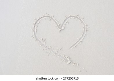 finger drawing on sandy beach heart , symbol of love.