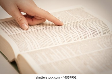 Finger of a female hand pointing a term on a book